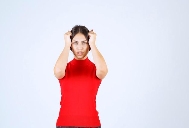 頭を抱えている赤いシャツを着た女の子が頭を手で押さえている。