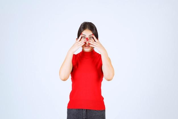 赤いシャツを着た女の子が指の間を覗き込んでいます。