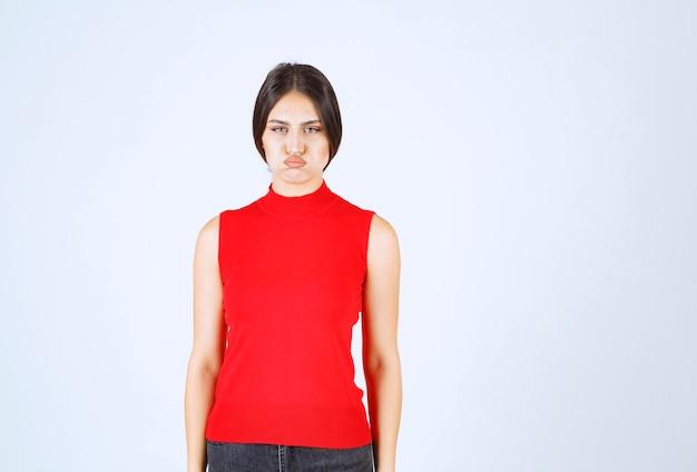 Девушка в красной рубашке выглядит недовольной.