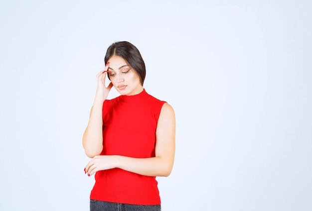 赤いシャツを着た女の子は、悲しくてがっかりしているように見えます。