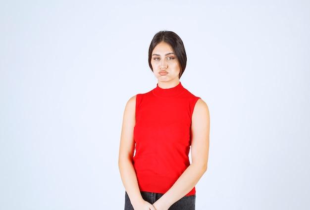 빨간 셔츠를 입은 소녀는 슬프고 실망 해 보입니다.