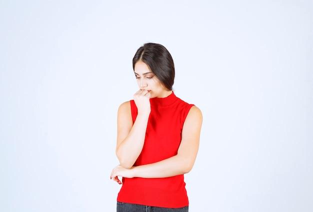 赤いシャツを着た女の子は、緊張して緊張しているように見えます。