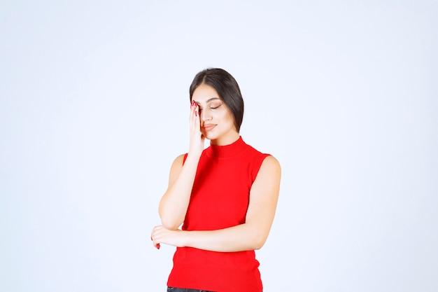 赤いシャツを着た女の子は疲れていて眠そうです。