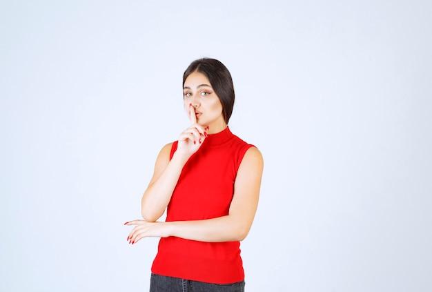 그녀의 입을 가리키고 침묵을 요구하는 빨간 셔츠에있는 소녀.