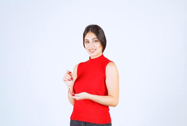 자신을 가리키는 빨간색 셔츠에 소녀입니다.