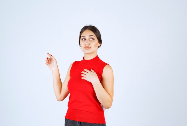 自分を指差す赤いシャツの女の子。