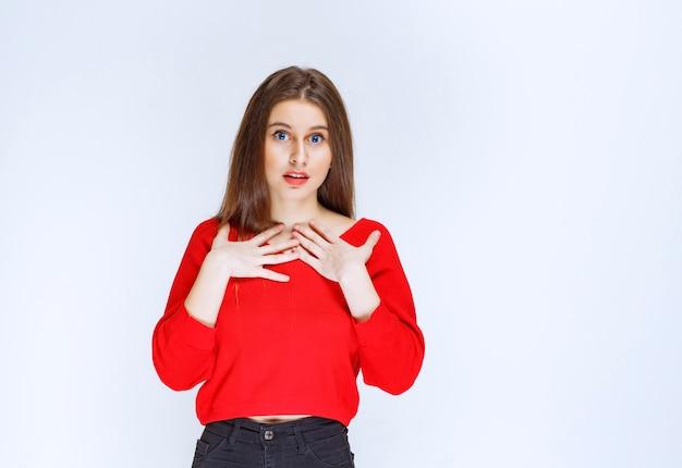자신을 가리키는 빨간 셔츠에 소녀입니다.