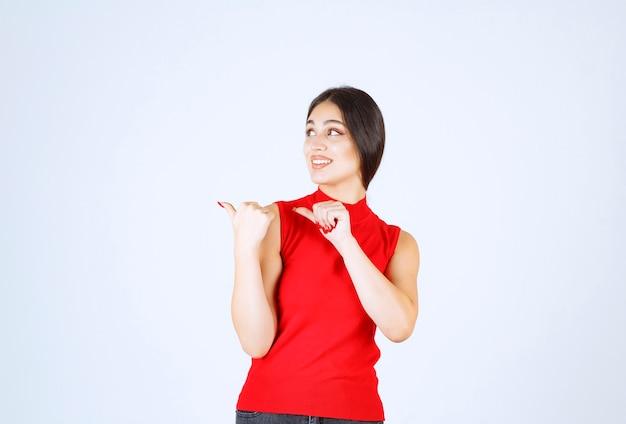 왼쪽에 뭔가 가리키는 빨간색 셔츠에 소녀.