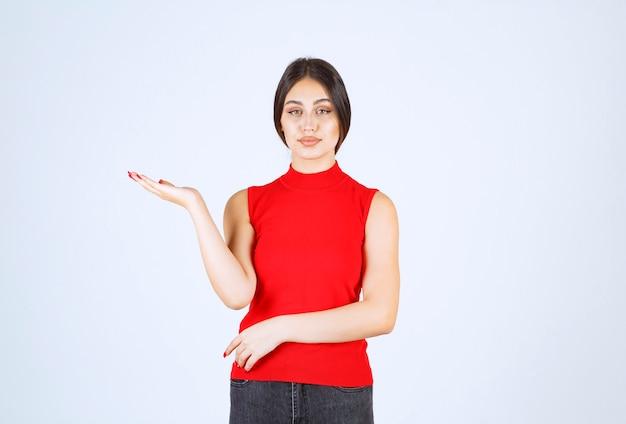 左の何かを指している赤いシャツの女の子。