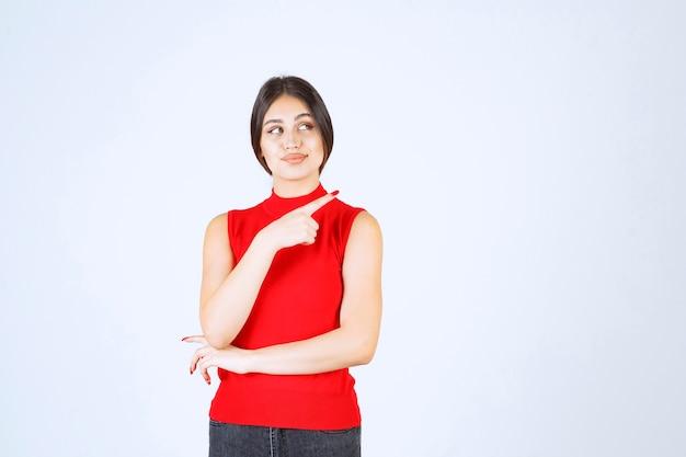 거꾸로 가리키는 빨간색 셔츠에 소녀입니다.