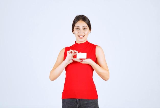 名刺を差し出す赤いシャツの女の子。