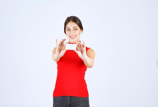 그녀의 명함을 제시하는 빨간 셔츠에있는 여자.