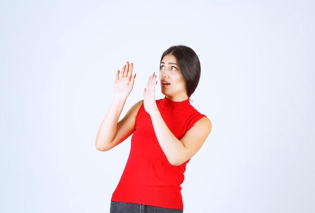 何かから身を守る赤いシャツの女の子。