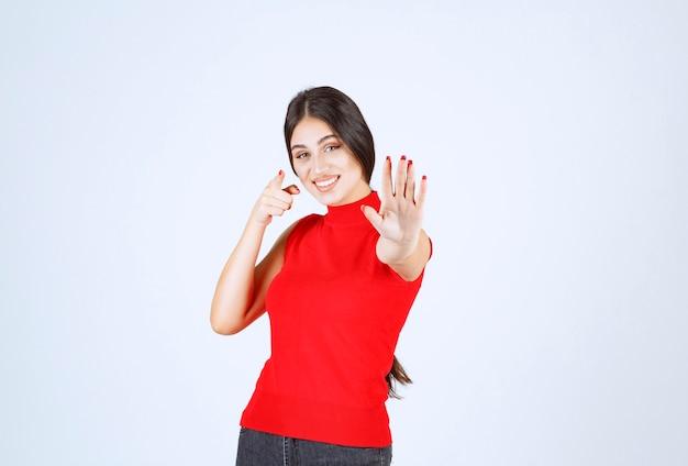 뭔가에서 자신을 방지하는 빨간 셔츠에있는 소녀.