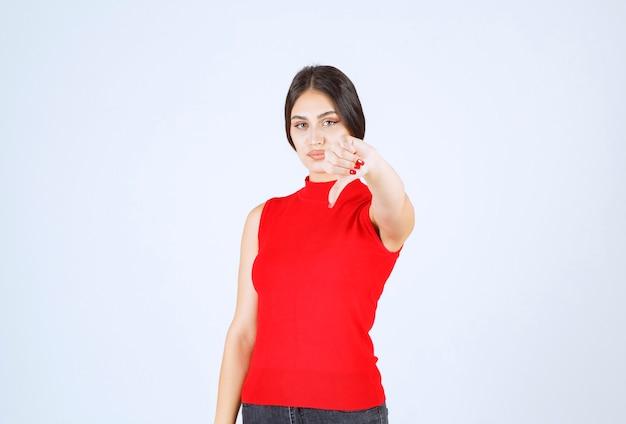 Девушка в красной рубашке показывает знак неприязни.