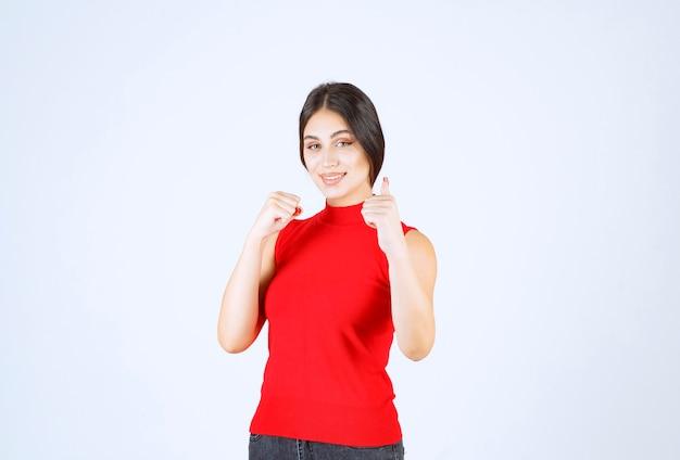 Девушка в красной рубашке показывая знак рукой удовольствия.