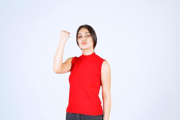 腕の筋肉と拳を見せる赤いシャツを着た女の子。