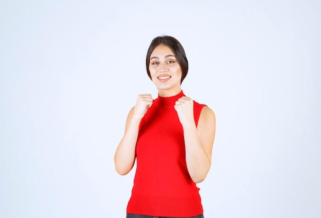 腕の筋肉と拳を見せる赤いシャツを着た女の子。 無料写真