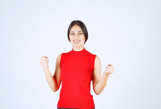 Девушка в красной рубашке показывает кулаки и силу.