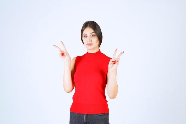 平和と友情のサインを示す赤いシャツの女の子。