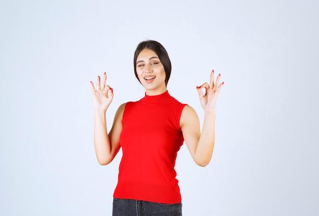 肯定的な手のサインを示す赤いシャツの女の子。