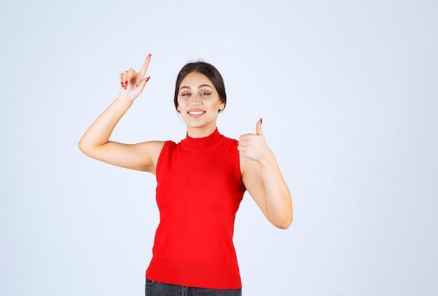 Девушка в красной рубашке показывает знак положительной руки.