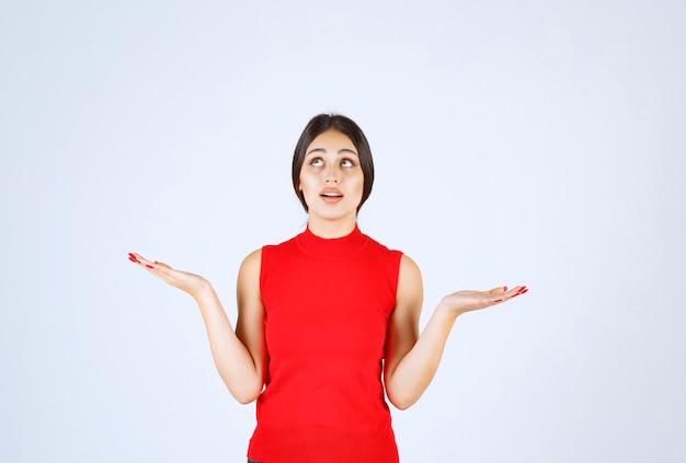 그녀의 손에 뭔가 보여주는 빨간색 셔츠에 소녀.