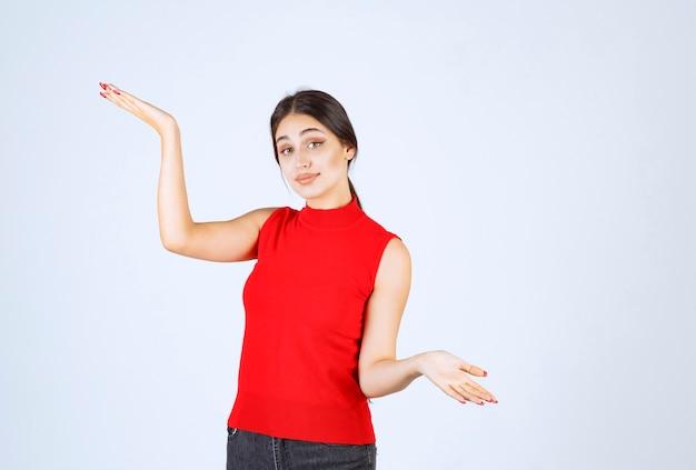 Девушка в красной рубашке показывает что-то в ее открытой руке.