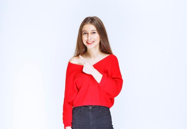 Девушка в красной рубашке показывает что-то слева.