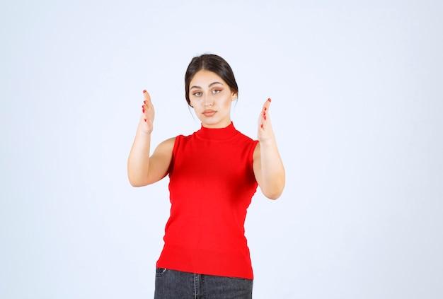 Девушка в красной рубашке показывает размер объекта.