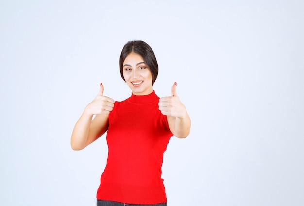 親指を立てる赤いシャツの女の子。