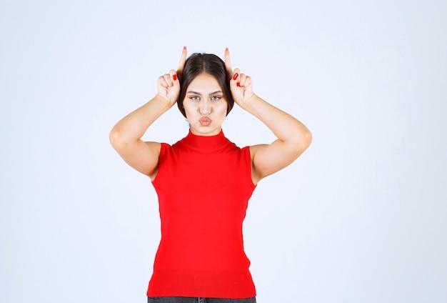 Девушка в красной рубашке показывает уши волка.