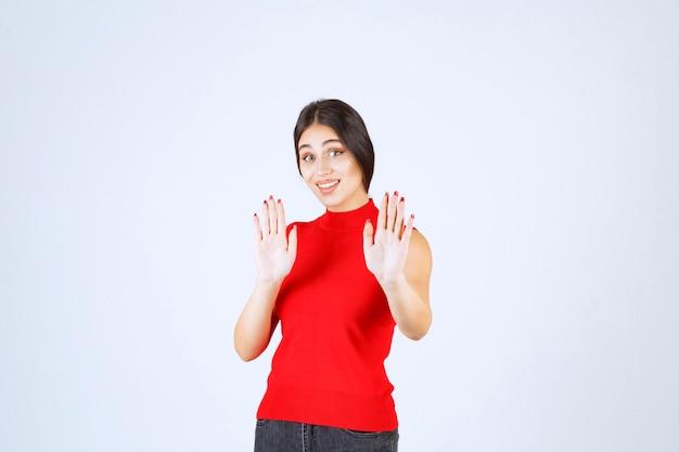 誰かを止める赤いシャツの女の子。