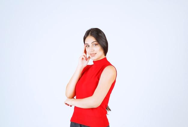 Девушка в красной рубашке думает и анализирует.