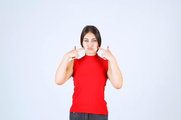 赤いシャツを着た女の子が考え、心をリフレッシュしている。