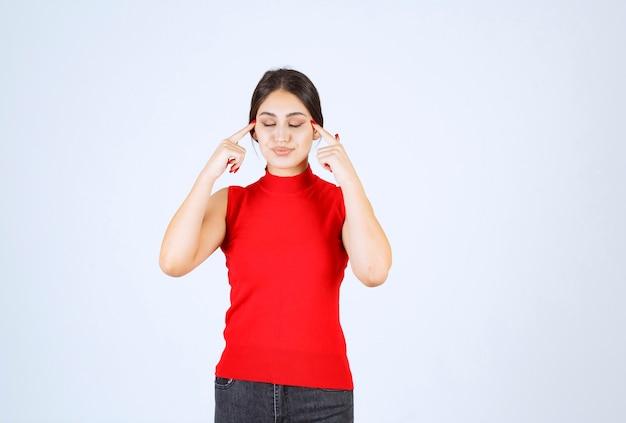 생각 하 고 그녀의 마음을 상쾌하게하는 빨간 셔츠에있는 여자.