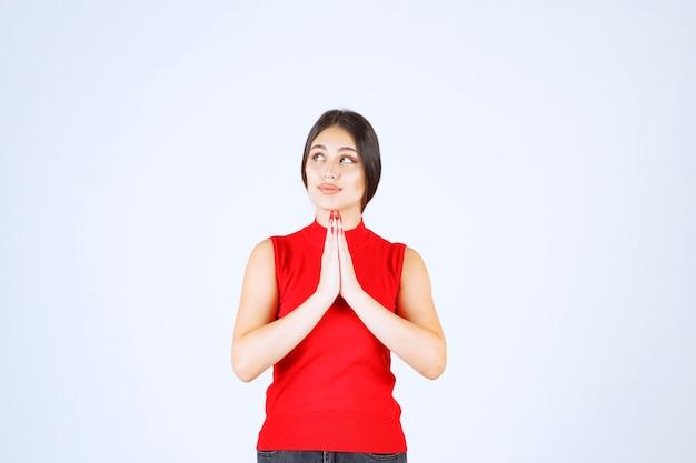 Девушка в красной рубашке объединяет руки и молится.