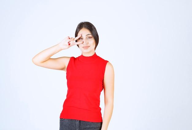 Девушка в красной рубашке подмигивает и показывает свое удовлетворение.