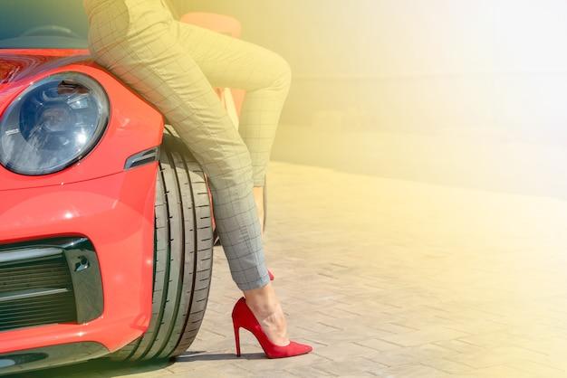 여름 화창한 날에 빨간 신발과 빨간 차 소녀.