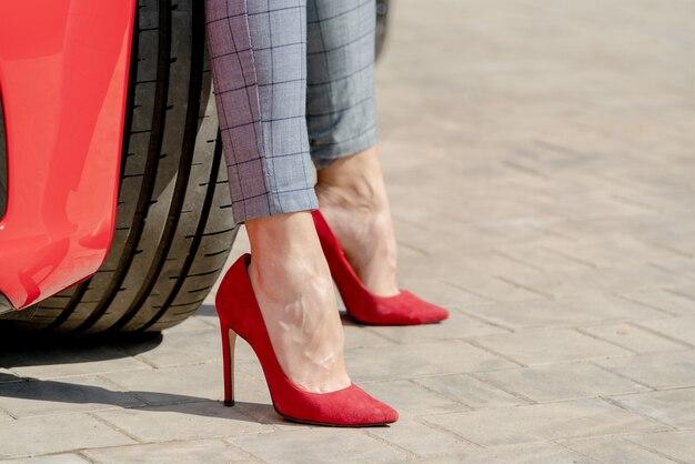 여름 화창한 날에 빨간 신발과 빨간 차 소녀. 프리미엄 사진