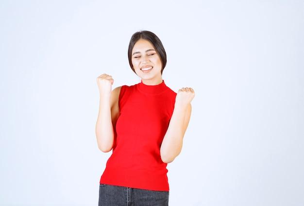 赤い服を着た女の子が拳を見せ、成功を感じている。