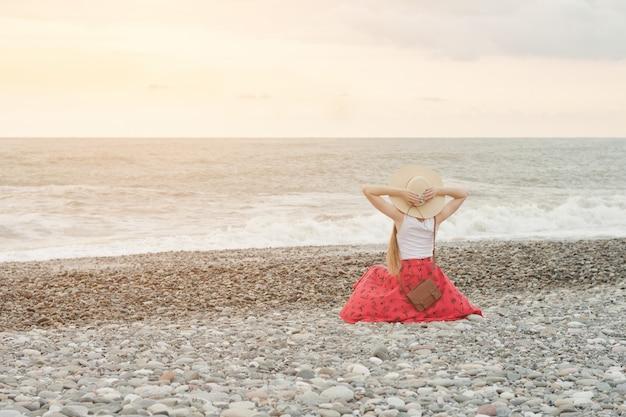Девушка в красной юбке и шляпе сидит на берегу моря. время заката вид сзади