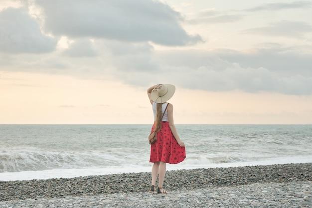 Девушка в красной юбке и шляпе готовя море, заход солнца. вид сзади