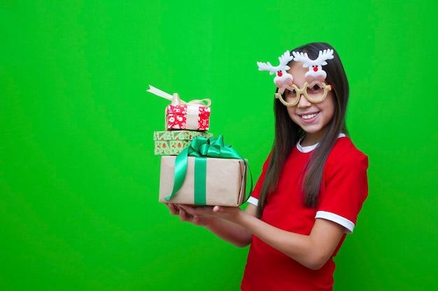 빨간 티셔츠를 입은 소녀가 손에 재미있는 안경을 들고 크리스마스 휴가를 위한 선물 상자를 들고 있다