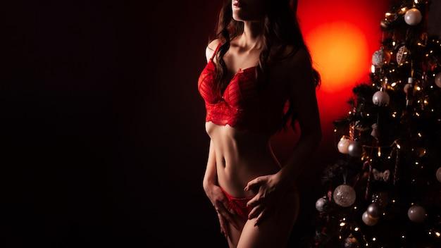 크리스마스 트리 옆에 섹시한 그림이 있는 빨간 속옷을 입은 소녀. 새해를 위한 에로틱한 선물의 개념