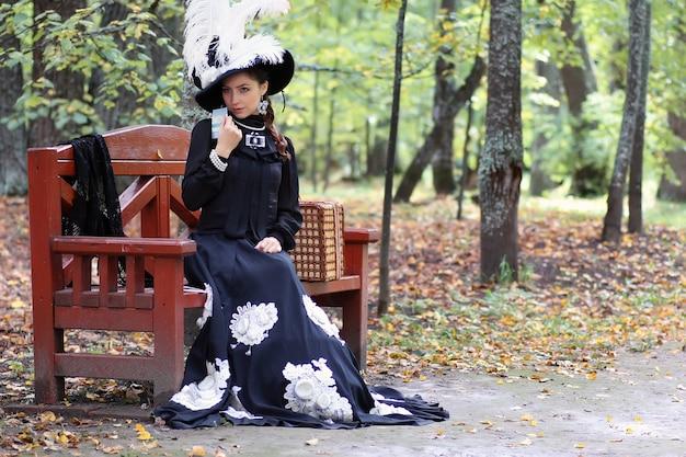 Девушка в ретро платье прошлого века читала письмо на скамейке
