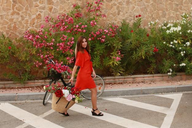 自転車に花のバスケットとレトロなドレスの女の子。美しい女性とかごの中の花。