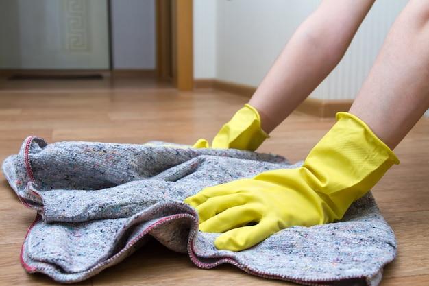 Девушка в резиновых перчатках моет пол дома тряпкой
