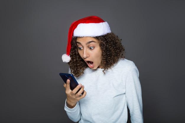 Девушка в шапке санта-клауса. молодая брюнетка с удивлением смотрит на мобильный телефон. концепция новогодних праздничных акций.