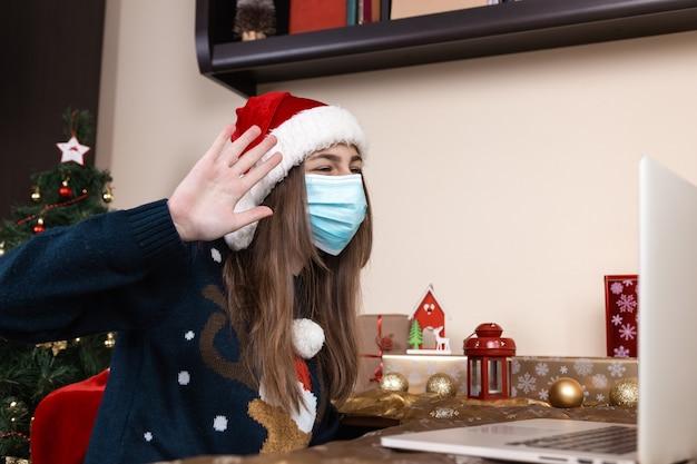 Девушка в шляпе санта-клауса в медицинских переговорах маски дает подарок, используя ноутбук для видеозвонков друзей и родителей. помещение празднично декорировано. рождество во время коронавируса.